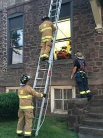 Warminster firefighters prepare to receive a down firefighter from an above grade window.