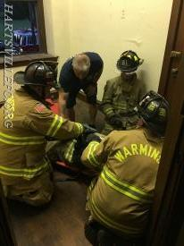 Firefighters prepare a firefighter to be removed from a window.