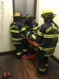 Firefighters transferring the down firefighter to a ladder.